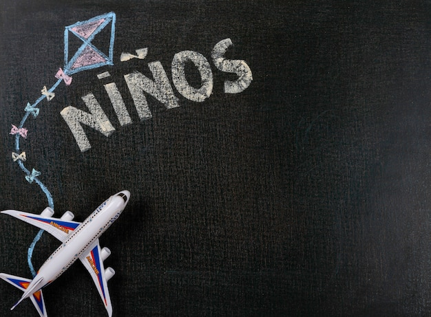 Drawing on blackboard. niños (spanish) written on blackboard and airplane toy. background copy space.