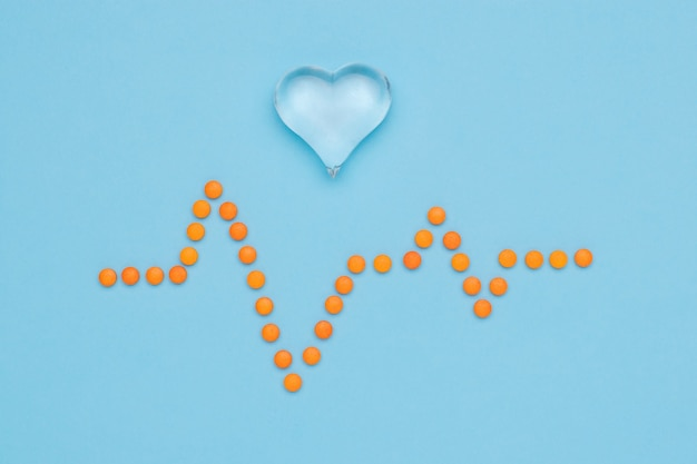 A drawing of a cardiogram made of orange pills and a glass heart on a blue surface