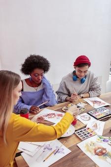 描画クラス。一緒に絵のクラスに参加する3人のファッショナブルな才能のある芸術の学生