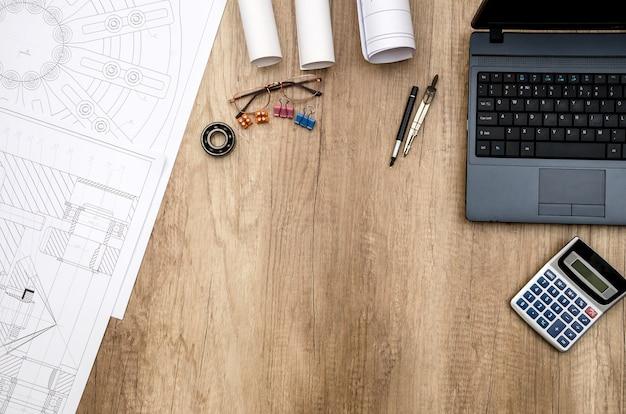 テーブルの上にラップトップを搭載したエンジニアリングツールを描く