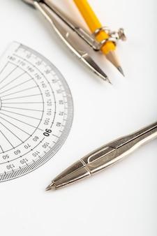 白の鉛筆で分離された金属のコンパスなどの図形を描く