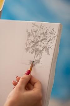 花を描く。花と花瓶を描く赤い爪を持つ有望なアーティストのクローズアップ