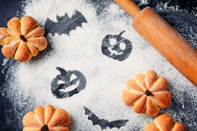 Drawing halloween decorations on flour background, cakes in a shape of pumpkin