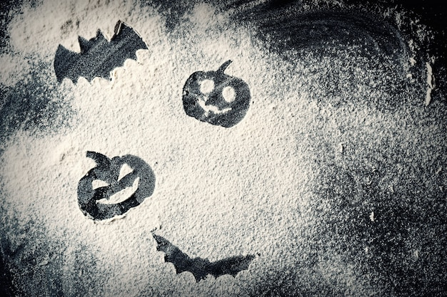 Drawing halloween pumpkin head jack lantern and bat on wheat flour background