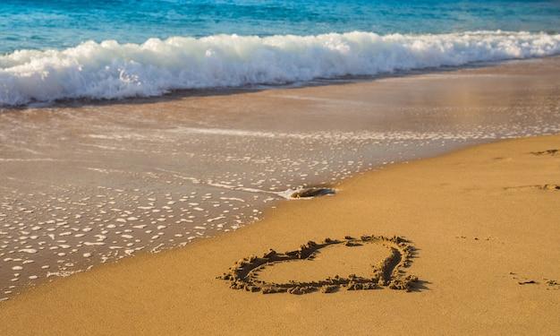 Drawing a heart on the beach sand near sea waves