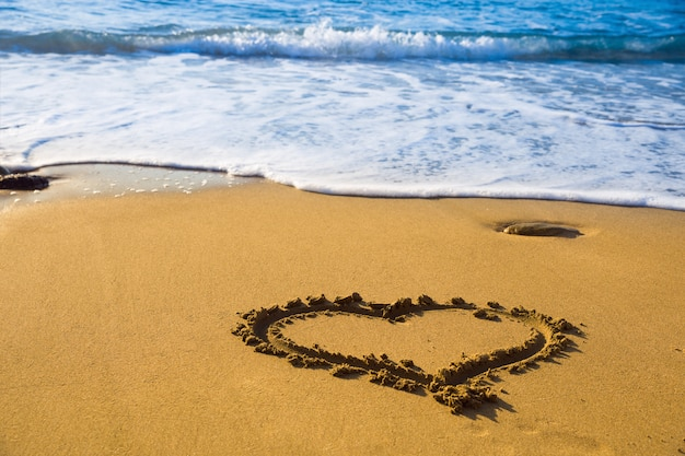 Drawing heart on beach sand with sea waves