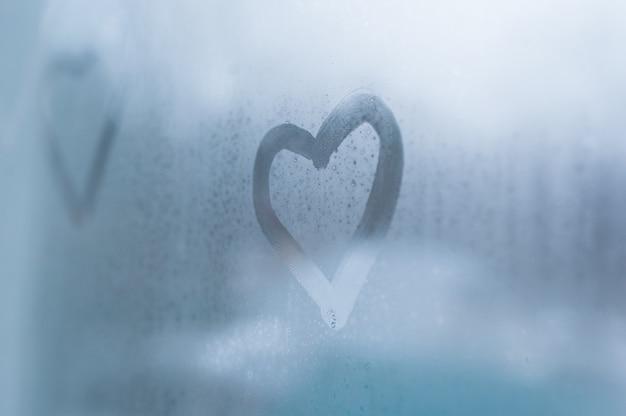 Drawing a heart on sweaty glass on window