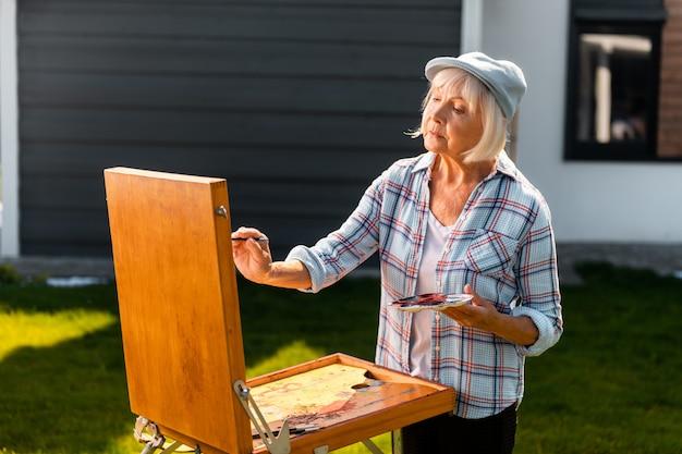 시골에서 그리기. 시골에서 그림을 그리는 동안 단순히 놀라움을 느끼는 은퇴 한 경험이 풍부한 아름다운 예술가