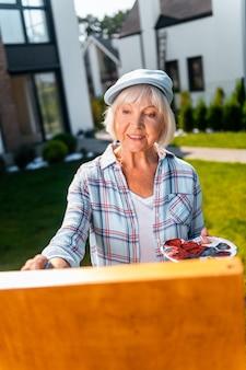 정원에서 그리기. 그녀의 정원에서 정물을 그리는 동안 진정으로 행복하고 쾌활한 느낌의 아름다운 노인 여성