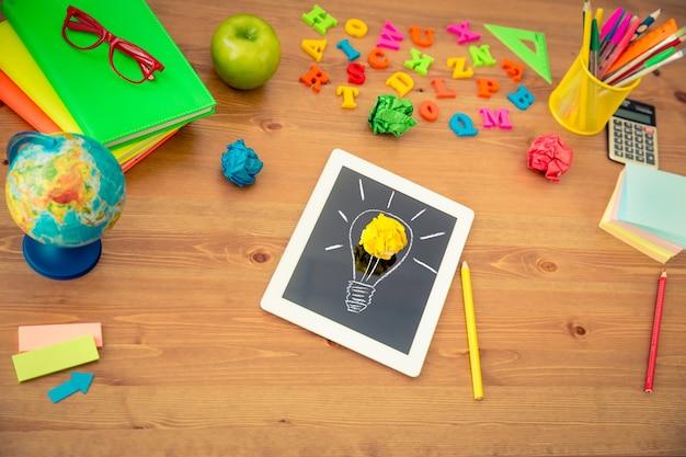 Рисование лампочки на планшетном пк. школьные принадлежности на деревянном столе в классе. концепция образования. вид сверху
