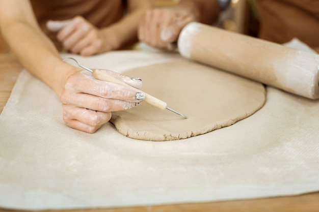 Рисование линий. известная искусная керамистка рисует линии на будущей керамической вазе, усердно работая