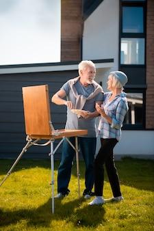 自然を描く。彼らの家の近くの庭に立っている間、一緒に自然を描く引退した男性と女性のカップル