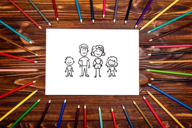 色鉛筆のフレームの白いテーブルにフェルトペンで作った家族の絵。家族の概念。上からの眺め