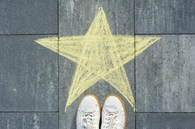 アスファルトの星と足にクレヨンを描く。