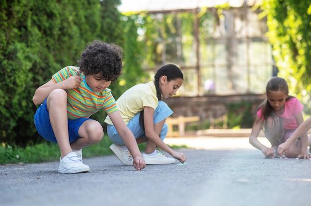 Рисунок на асфальте. сосредоточенные молодые друзья рисуют мелками на дороге в зеленом парке в солнечный день