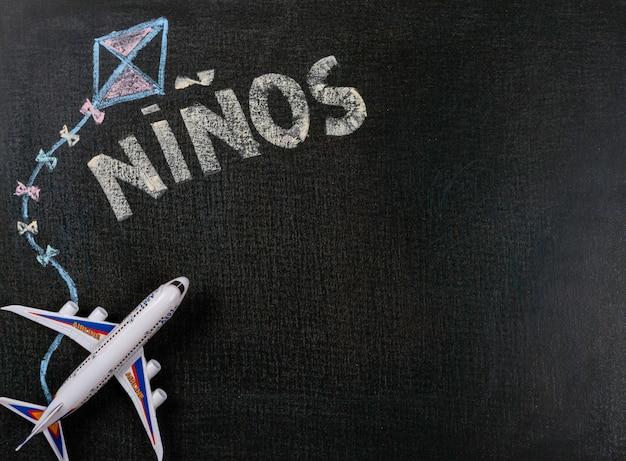 칠판에 그리기. 칠판과 비행기 장난감에 니뇨 (스페인어). 배경 복사 공간.