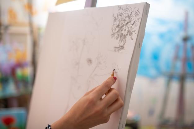 キャンバスに描画します。白いキャンバスに赤い爪で描く若い有望なアーティストのクローズアップ