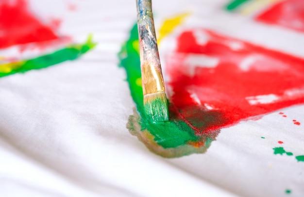 Опираясь на одежду. девушка рисует на белой футболке.