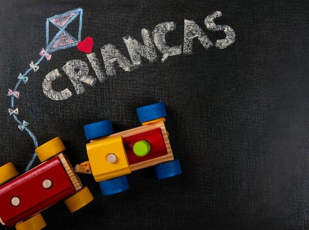サンドペーパーでの描画。黒板に書かれたcrianças(ポルトガル語)と作品の組み立て。コピースペース