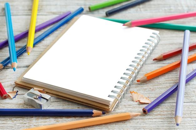 Блокнот и цветные карандаши на деревянном столе