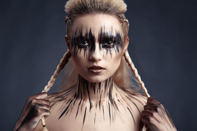 女性の顔と体に絵の具を描く