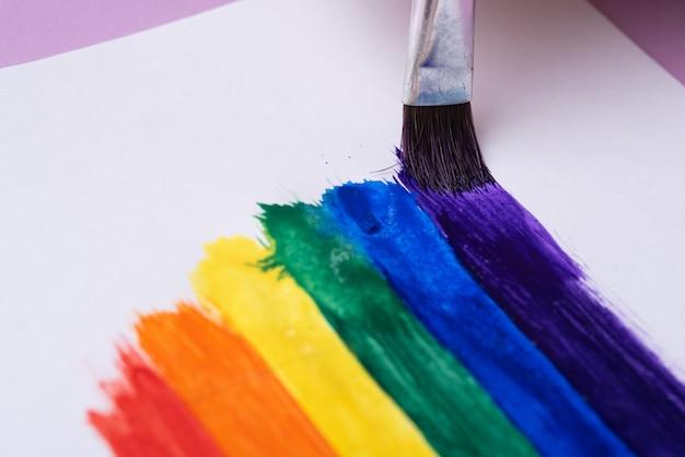 Рисование радуги, радужных полос акварельной краской с использованием кисти, крупным планом, концепция символа лгбтк