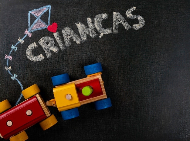 Drawing on sandpaper. crianças (portuguese) written on blackboard and assembling pieces. copy space