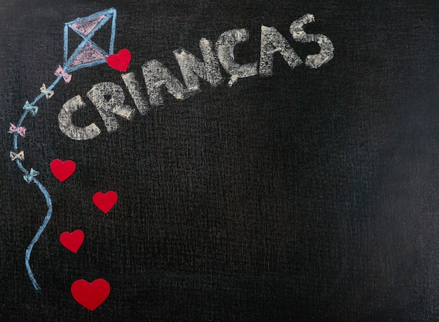 Drawing on sandpaper. crianças (portuguese) written on chalkboard and hearts. background copy space.