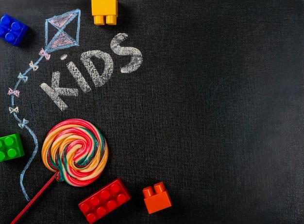 Drawing on sandpaper. kids written on blackboard and lollipop. background copy space.