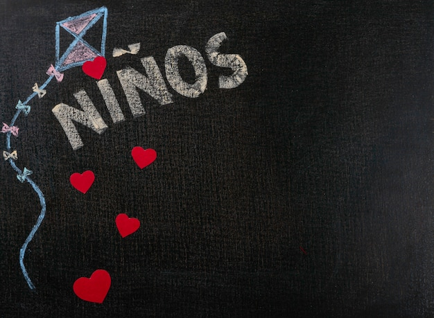 Drawing on sandpaper. niños (spanish) written on blackboard and hearts. background copy space