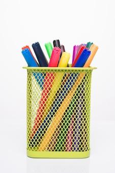 Концепция расходных материалов для рисования. фотография красочных маркеров в желтой чашке карандаша, изолированные на белом фоне