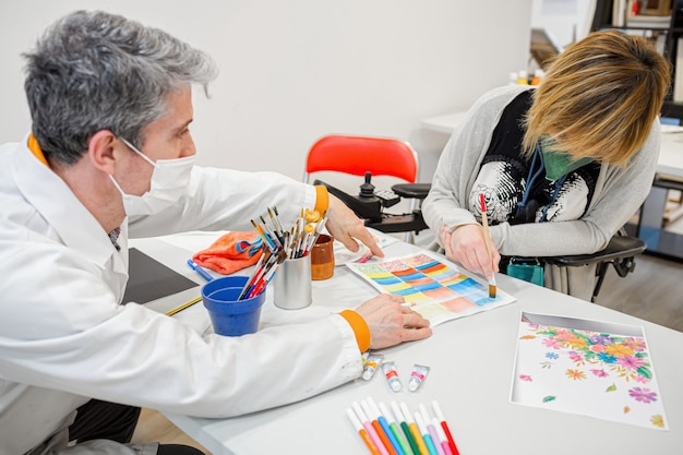 Drawing teacher teaching a handicapped student in a wheelchair