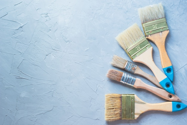 Drawing tools paintbrushes on gray cement background, top view