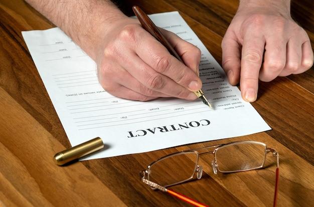 데스크탑의 작업 환경에서 계약서 작성. 펜으로 빈 작성 남자 손 클로즈업