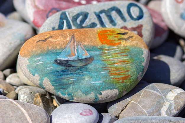The drawing watercolor paints on a beach stone