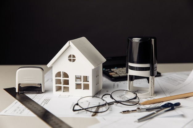 Drawing with model of house calculator and stamps building business and investment concept