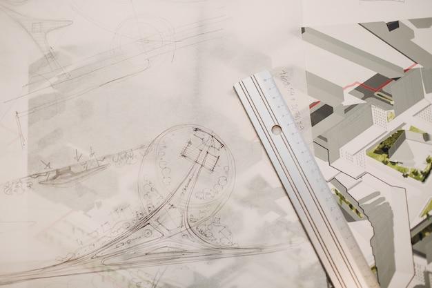 Чертежи чертежей и дизайн-проект макета за офисным столом с линейкой.