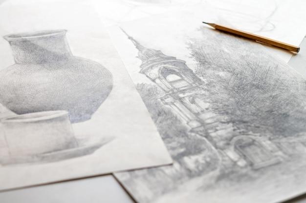Рисунки, сделанные карандашом, лежат на столе.