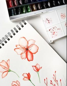 Рисунки, палитра и акварельные краски вид сверху