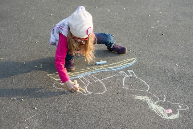 Drawings on the sidewalk, girl child draws a unicorn