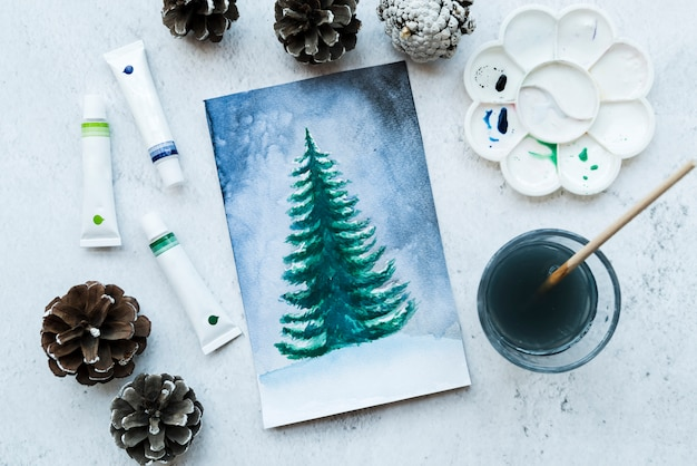 Drawn christmas tree canvas with pinecones; color tubes and paint brush on textured backdrop