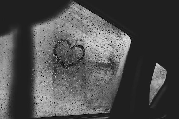 雨上がりの濡れた車の窓に描かれたハート。閉じる。黒と白の写真
