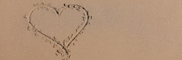 Нарисованное сердце на мокром песке рядом с морем