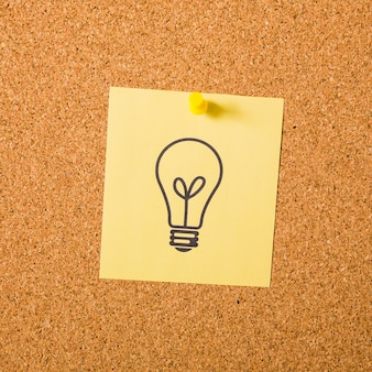 Drawn light bulb on adhesive note attached with pushpin on notice board