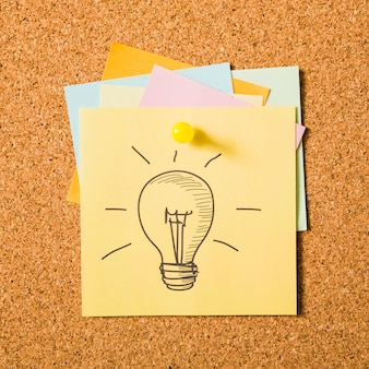 Drawn light bulb icon on adhesive note attached with pushpin