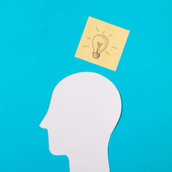 Drawn light bulb icon on sticky note over the paper cut out head against blue background