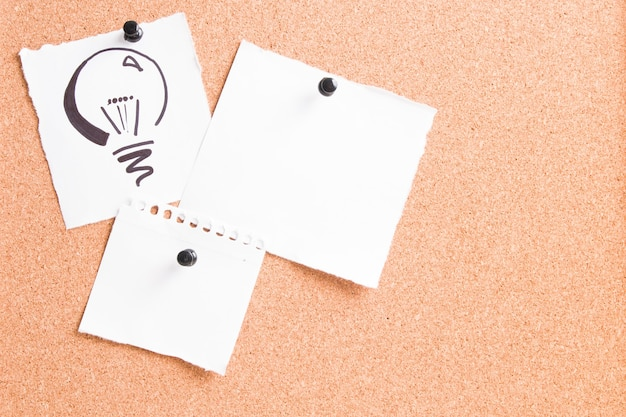 Нарисованная лампочка на белом листе, прикрепленная к пробковой доске булавкой с другими бумагами