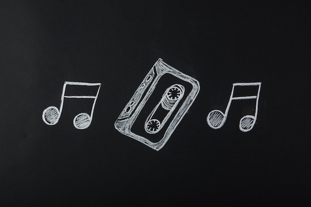 Drawn musical notes with cassette tape on blackboard