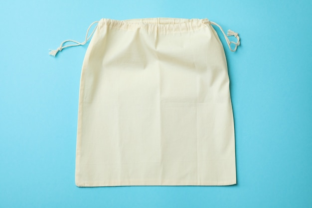 Drawstring eco bag on blue surface, space for text