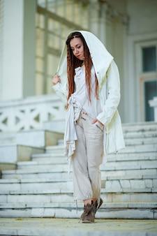 古い宮殿の背景にポーズをとって白い服を着たドレッドヘアのファッショナブルな女の子